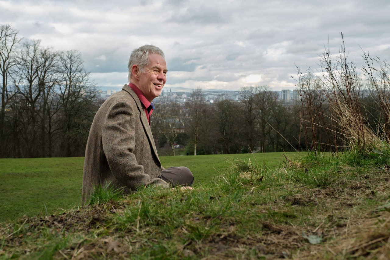 banner image of Martin sitting on a grassy hill